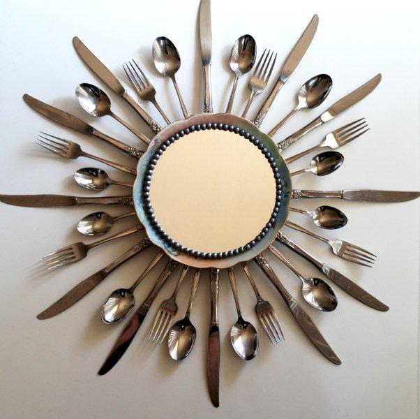 a starburst mirror with forks, spoons and knifes