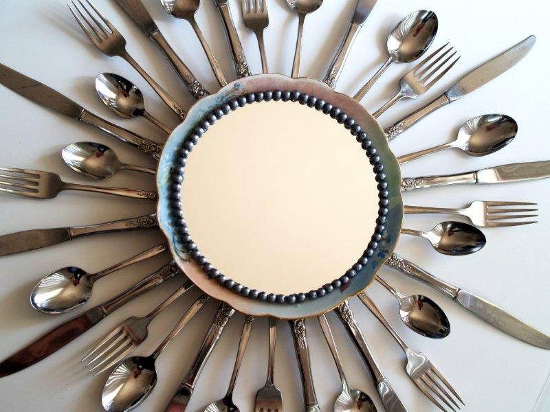 a picture of a mirror with a cutlery border