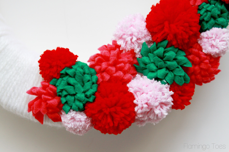 Pom poms and flowers on wreath