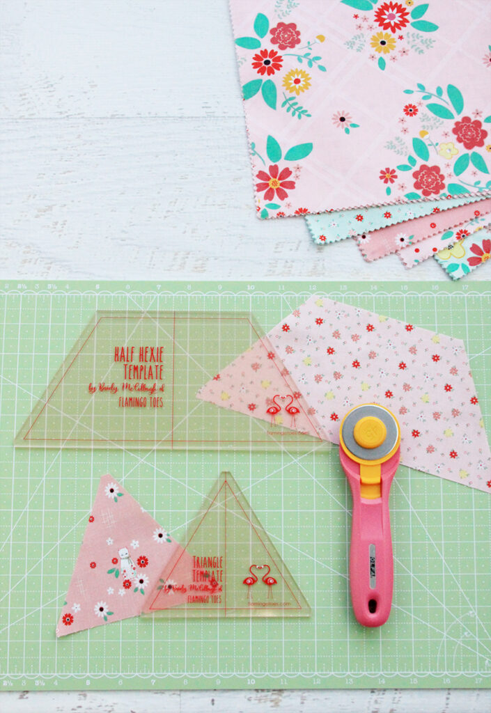 New Quilting Templates on the Way! by popular Tennessee quilting blog, Flamingo Toes: image of the half hexie  and triangle template on a green rotary board next to a rotary cutter.